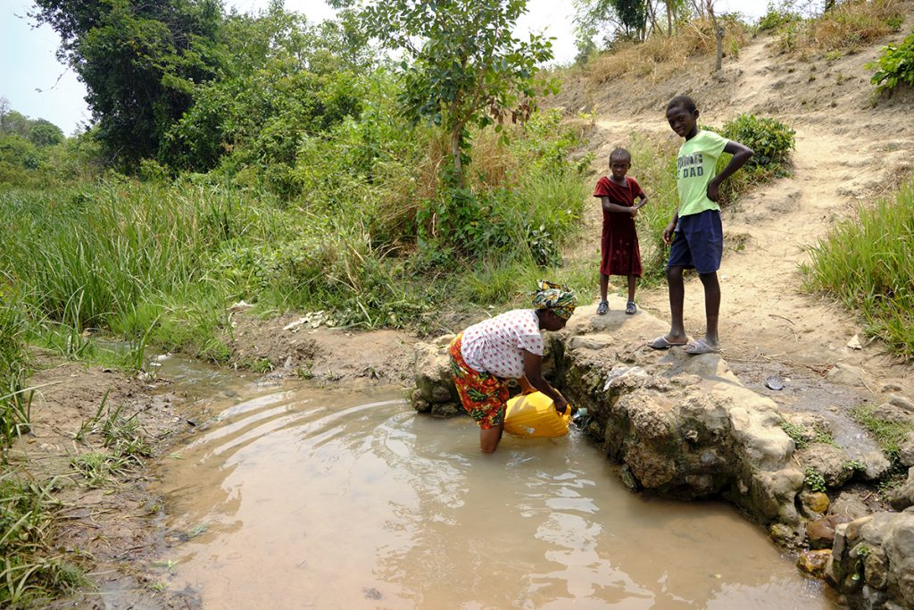Mujer recogiendo agua (contaminada) para beber, cocinar, etc.
