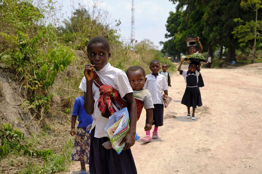 Niñas, estudiantes, cargando a su hermano menor, al carbón y las verduras, mientras sus hermanos solo llevan el cuaderno.